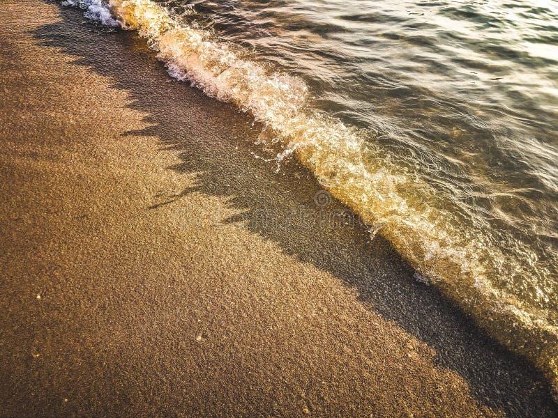 όμορφη ηλιόλουστη αμμώδης παραλία με πολύχρωμο ουρανό και δραματικά σύννεφα πάνω από κυματιστή θάλασσα στοκ φωτογραφία με δικαίωμα ελεύθερης χρήσης