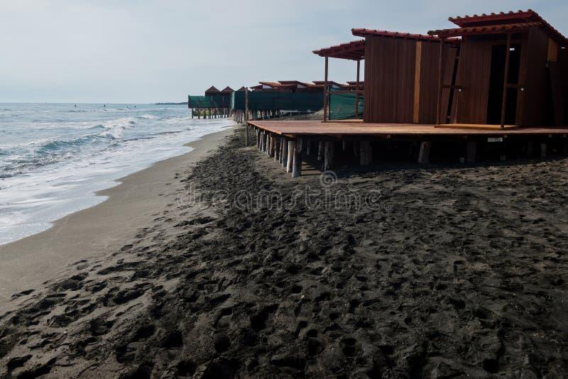 Όμορφη θάλασσα, η μαύρα αμμώδη παραλία και τα σπίτια παραλιών στοκ φωτογραφία