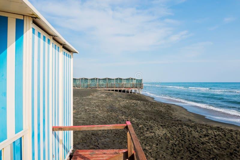 Όμορφη θάλασσα, η μαύρη αμμώδης παραλία και τα άσπρα και μπλε ριγωτά σπίτια παραλιών στοκ εικόνα