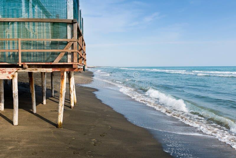 Όμορφη θάλασσα, η μαύρη αμμώδης παραλία και τα άσπρα και μπλε ριγωτά σπίτια παραλιών στοκ εικόνα με δικαίωμα ελεύθερης χρήσης
