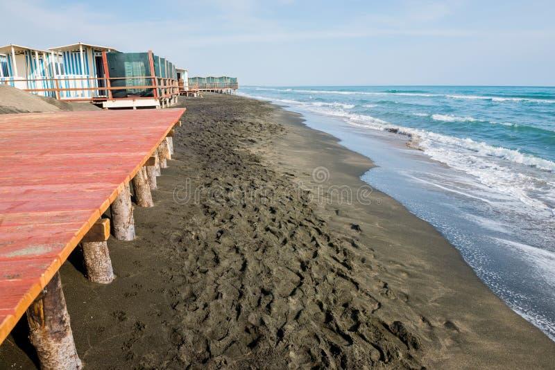 Όμορφη θάλασσα, η μαύρη αμμώδης παραλία και τα άσπρα και μπλε ριγωτά σπίτια παραλιών στοκ εικόνες
