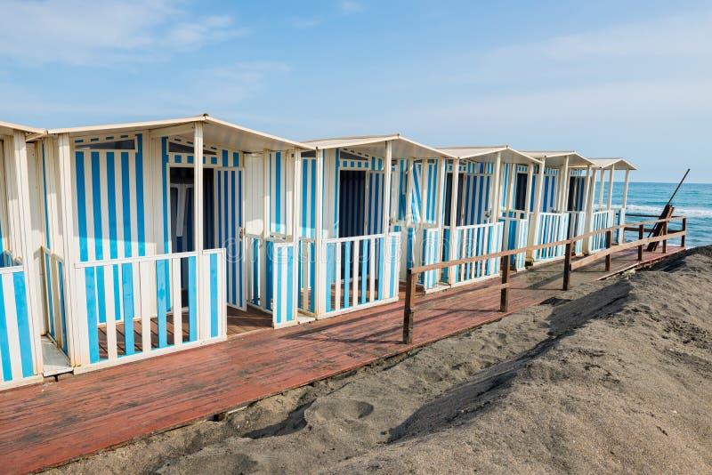 Όμορφη θάλασσα, η μαύρη αμμώδης παραλία και τα άσπρα και μπλε ριγωτά σπίτια παραλιών στοκ φωτογραφίες