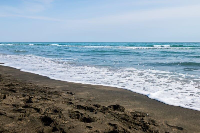 Όμορφη θάλασσα και η μαύρη αμμώδης παραλία, στοκ εικόνες