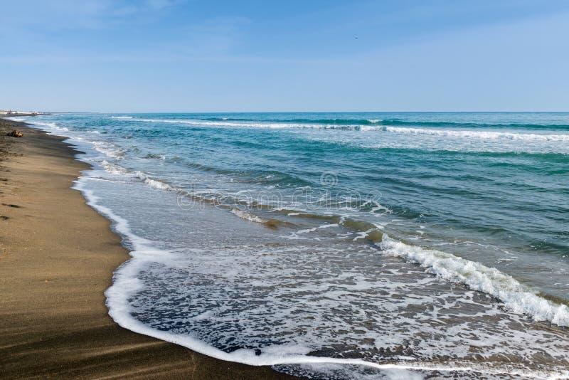 Όμορφη θάλασσα και η μαύρη αμμώδης παραλία, στοκ εικόνα