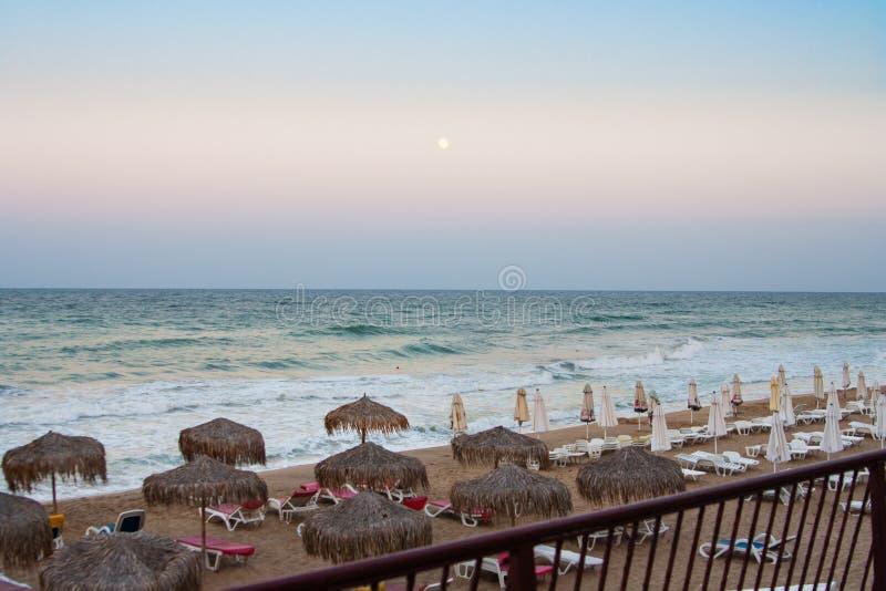 όμορφη θάλασσα τοπίων Γκρίζα κενά sunbeds ουρανού ηλιοβασιλέματος σε μια εγκαταλειμμένη παραλία Το τέλος της ημέρας παραλιών στοκ εικόνες