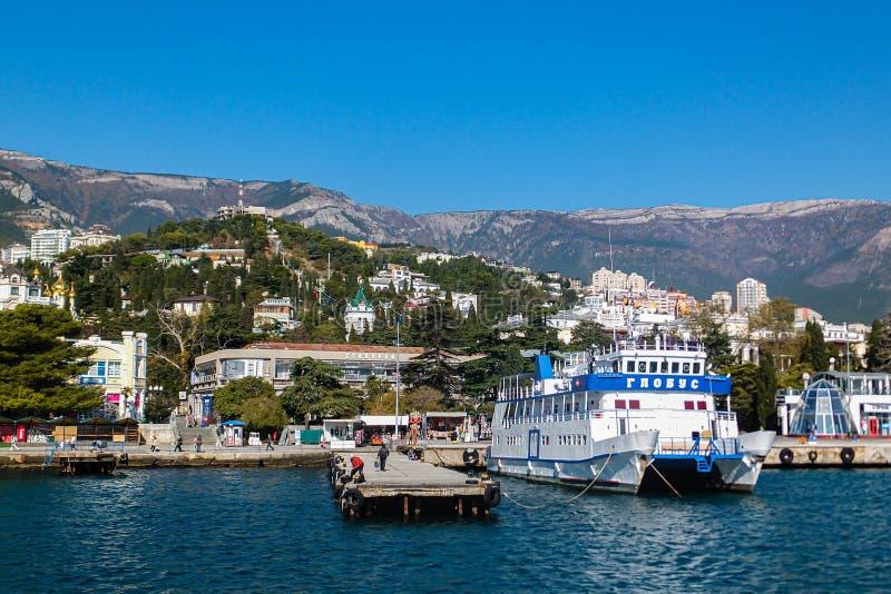 Όμορφη θέα του θέρετρου Crimean Yalta από τη Μαύρη Θάλασσα Γαλάζιο νερό, λευκό πλοίο και κτίρια στοκ εικόνα με δικαίωμα ελεύθερης χρήσης