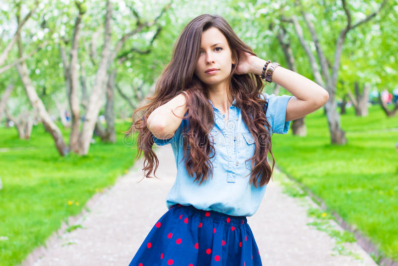 Όμορφη θερινή γυναίκα με τη σγουρή τρίχα στο πράσινο πάρκο στοκ εικόνες