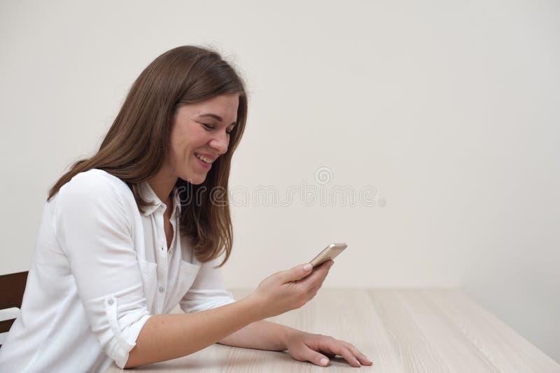 Όμορφη θετική νέα γυναίκα με το smartphone στοκ εικόνες