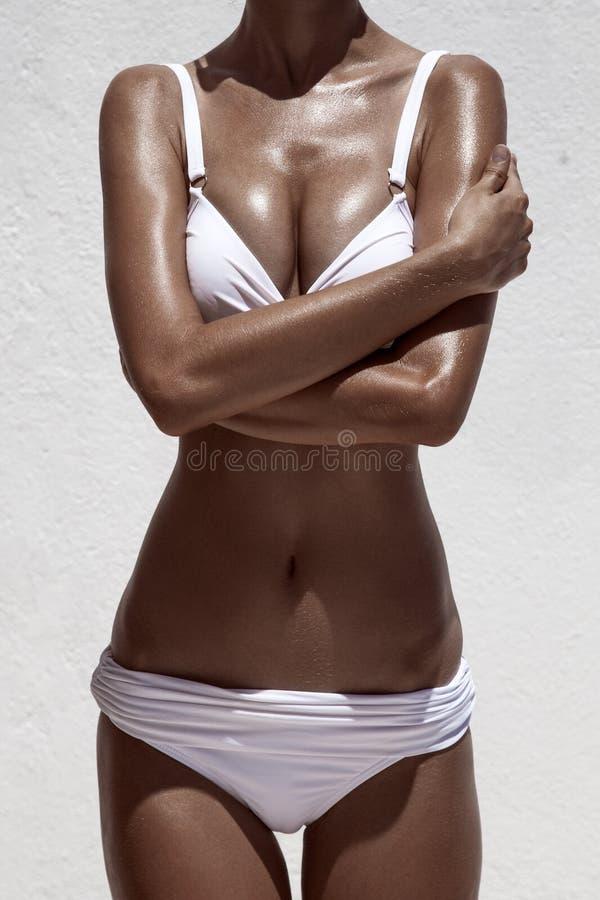Όμορφη θηλυκή πρότυπη τοποθέτηση μαυρίσματος στοκ εικόνες