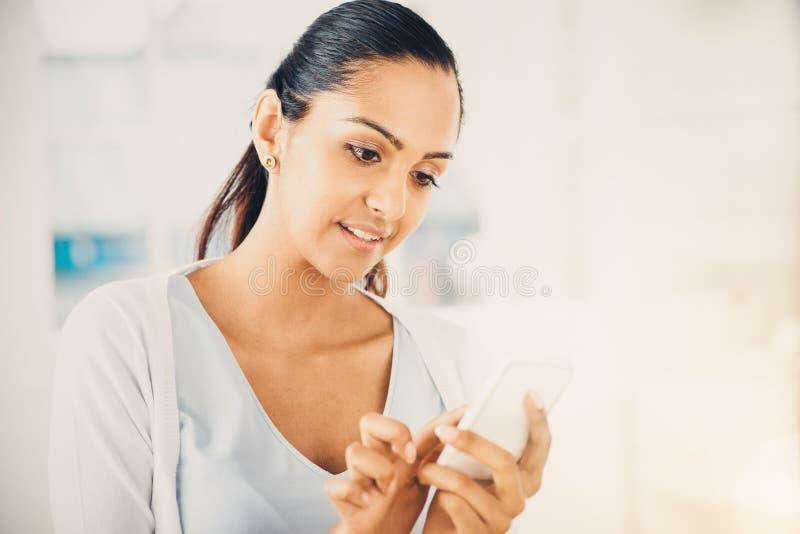 Όμορφη ινδική γυναίκα που στέλνει στο μήνυμα κειμένου το κινητό τηλέφωνο ευτυχές στοκ εικόνα