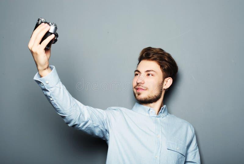 Όμορφη κάμερα εκμετάλλευσης νεαρών άνδρων και παραγωγή selfie στοκ φωτογραφία με δικαίωμα ελεύθερης χρήσης