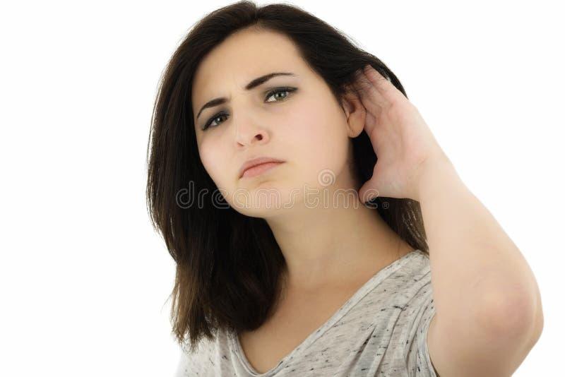 Όμορφη και ελκυστική χειρονομία ακούσματος κοριτσιών άνω της λευκιάς ΤΣΕ στοκ εικόνες