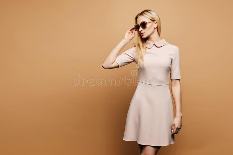 Όμορφη και κομψή νέα πρότυπη ξανθή κυρία στα μοντέρνα γυαλιά ηλίου και το μπεζ κοντό φόρεμα, με τη χρυσή τοποθέτηση σκουλαρικιών στοκ εικόνα