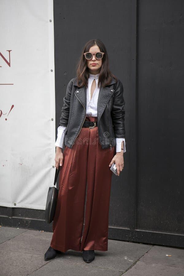 Όμορφη και μοντέρνη γυναίκα Α στο παντελόνι μαύρων δέρματος σακακιών και κλαρέ που θέτει κατά τη διάρκεια της εβδομάδας μόδας του στοκ φωτογραφία με δικαίωμα ελεύθερης χρήσης