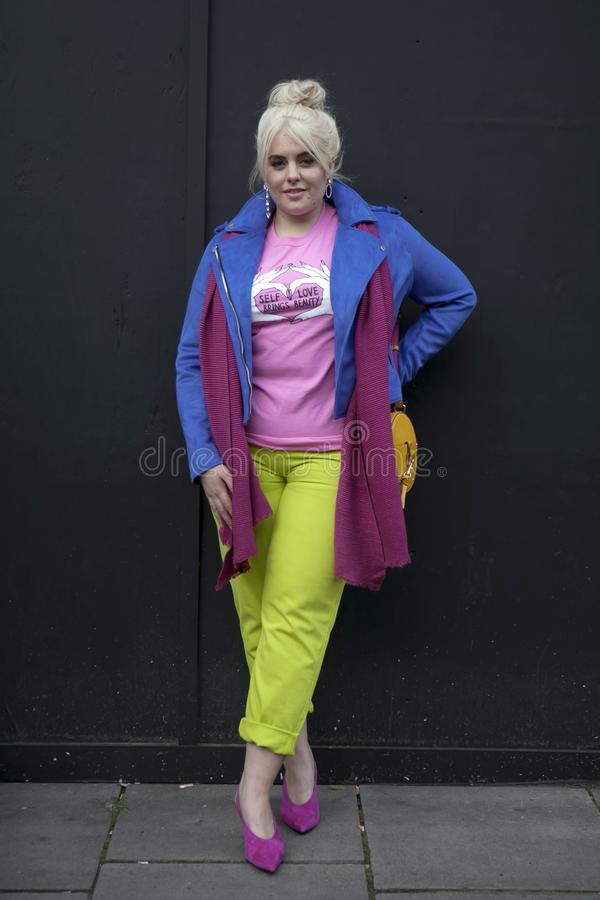 Όμορφη και μοντέρνη γυναίκα στο μπλε παλτό, τη ρόδινη μπλούζα και το κίτρινο παντελόνι που θέτουν κατά τη διάρκεια της εβδομάδας  στοκ εικόνες