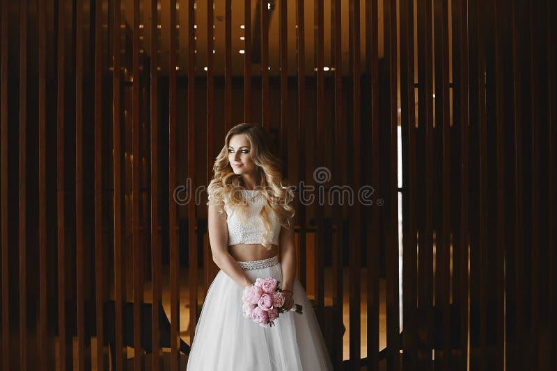 Όμορφη και προκλητική ξανθή πρότυπη γυναίκα με το τέλειο σώμα σε μια μοντέρνη φούστα του Tulle και στη μοντέρνη μπλούζα που κρατά στοκ φωτογραφίες με δικαίωμα ελεύθερης χρήσης