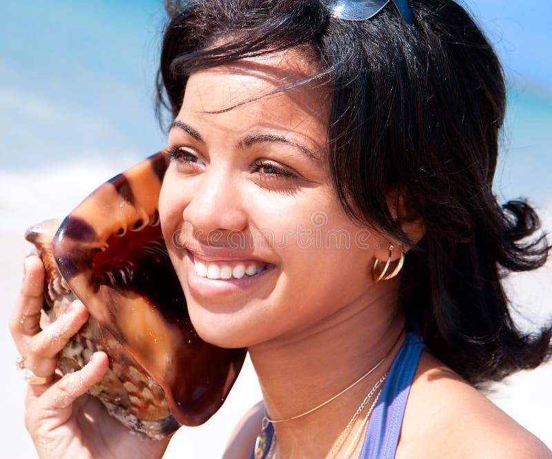 Όμορφη καραϊβική γυναίκα που κρατά ένα κοχύλι conch στοκ εικόνα με δικαίωμα ελεύθερης χρήσης