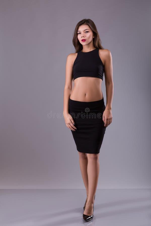 Όμορφη κατάλληλη γυναίκα με τον κοντή μαύρη στηθόδεσμο ή την κορυφή και φούστα στο γκρίζο υπόβαθρο στούντιο στοκ εικόνα