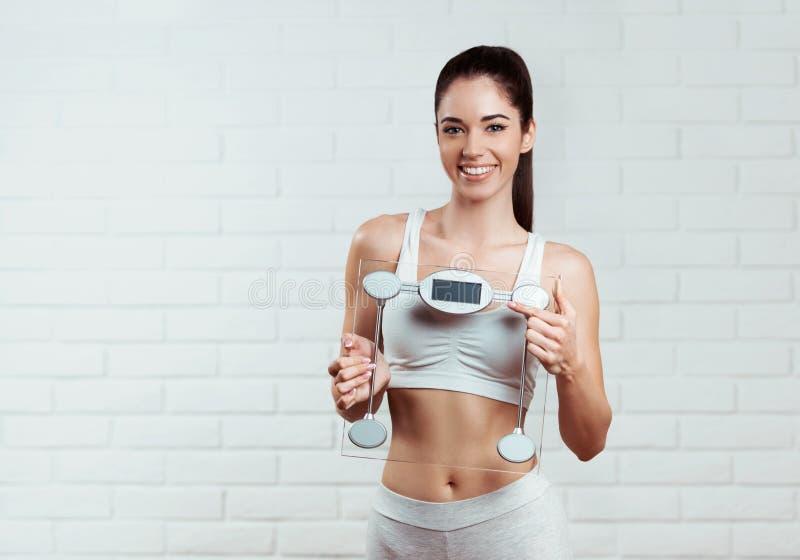Όμορφη, κατάλληλη, νέα γυναίκα που κρατά μια κλίμακα βάρους στοκ εικόνες