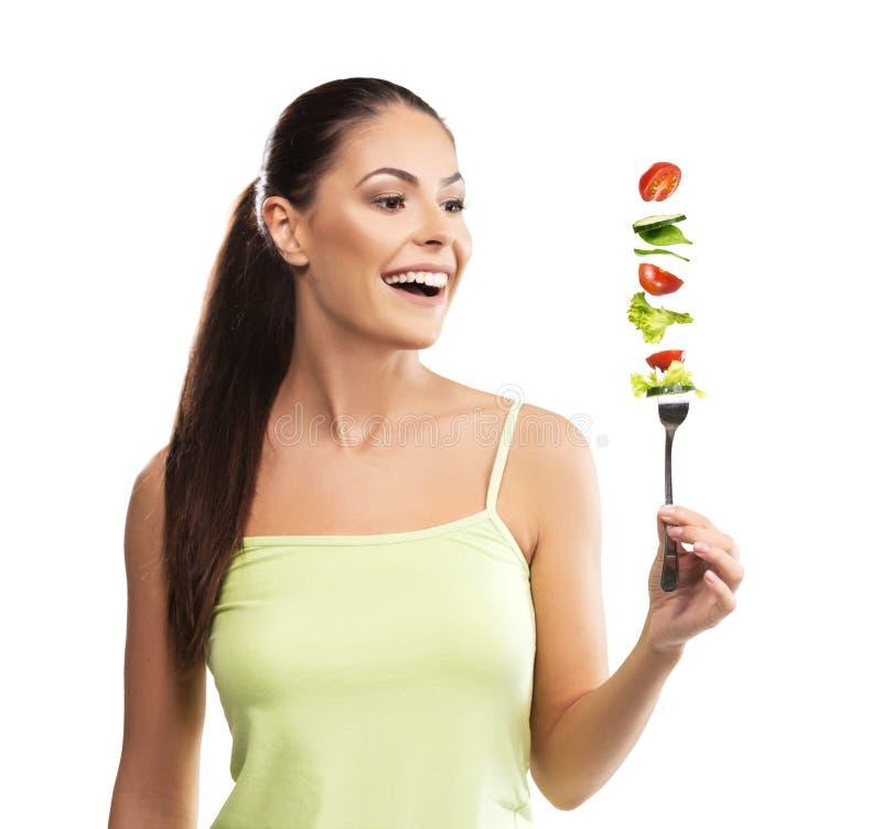 Όμορφη, κατάλληλη νέα γυναίκα που κρατά ένα δίκρανο με τα λαχανικά στοκ εικόνα