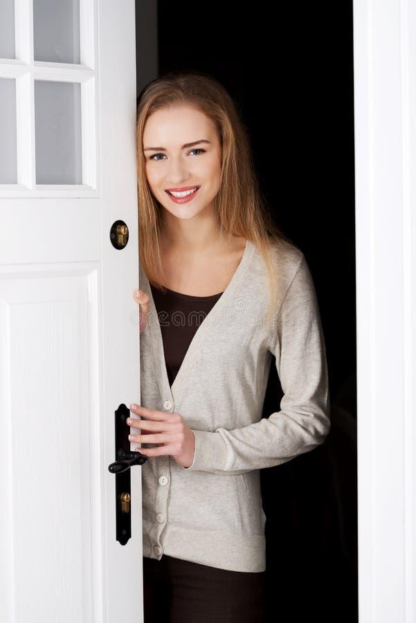 Όμορφη καυκάσια γυναίκα που υπερασπίζεται την πόρτα. στοκ εικόνες