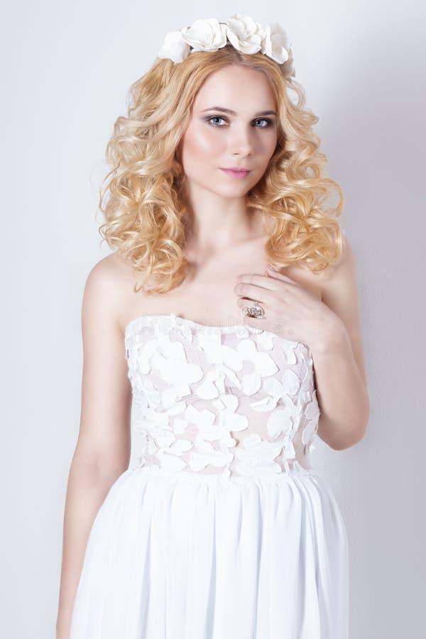 Όμορφη καλή ευγενής κομψή νέα ξανθή γυναίκα σε ένα άσπρο σιφόν και τις μπούκλες sundress, και ένα στεφάνι των λουλουδιών στην τρί στοκ εικόνες
