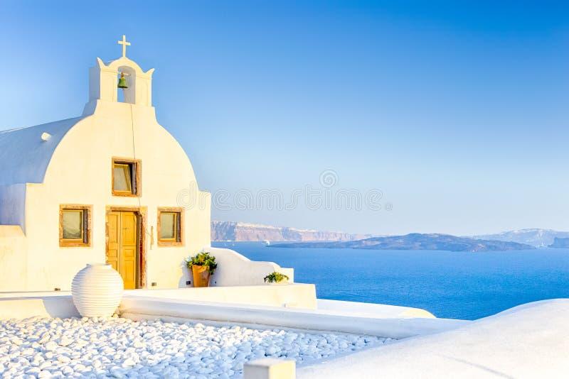 Όμορφη κλασική άσπρη εκκλησία Roofed με το επίπεδο αέτωμα και κουδούνι ενάντια ηφαιστειακό Caldera Oia στο νησί σε Santorini στην στοκ εικόνες