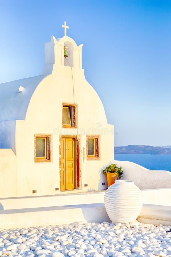 Όμορφη κλασική άσπρη εκκλησία Roofed με το επίπεδο αέτωμα και κουδούνι ενάντια ηφαιστειακό Caldera Oia στο νησί σε Santorini στην στοκ φωτογραφία με δικαίωμα ελεύθερης χρήσης