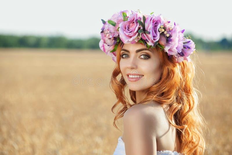 Όμορφη κοκκινομάλλης γυναίκα σε ένα στεφάνι λουλουδιών σε έναν τομέα σίτου στοκ φωτογραφία με δικαίωμα ελεύθερης χρήσης