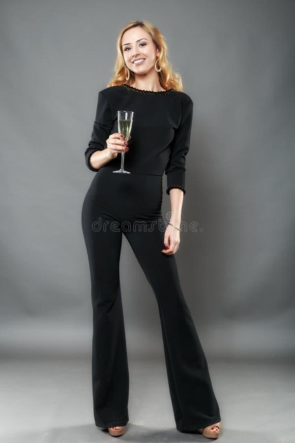 Όμορφη κομψή γυναίκα με ένα γυαλί του διαθέσιμου χεριού σαμπάνιας isolat στοκ εικόνες