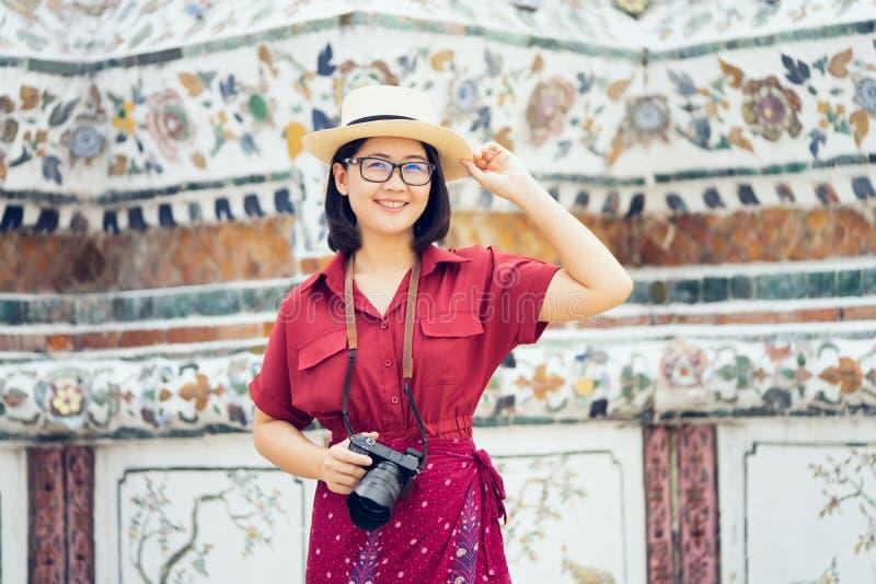 Όμορφη κρατημένη τουρίστας κάμερα γυναικών για να συλλάβει τις μνήμες Ναός Arun Wat στην Ταϊλάνδη χρησιμοποίηση ως έννοια ταξιδιο στοκ φωτογραφίες