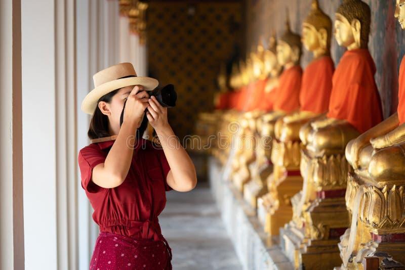 Όμορφη κρατημένη τουρίστας κάμερα γυναικών για να συλλάβει τις μνήμες Ναός Arun Wat στην Ταϊλάνδη χρησιμοποίηση ως έννοια ταξιδιο στοκ φωτογραφία