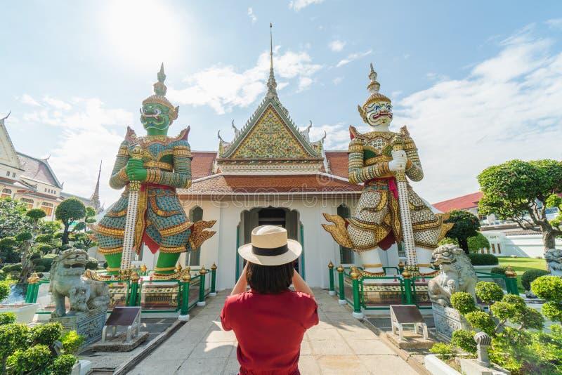 Όμορφη κρατημένη τουρίστας κάμερα γυναικών για να συλλάβει τις μνήμες Ναός Arun Wat στην Ταϊλάνδη χρησιμοποίηση ως έννοια ταξιδιο στοκ εικόνες