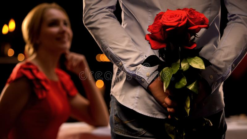 Όμορφη κυρία ευτυχής να δει το φίλο με τη δέσμη των τριαντάφυλλων, γεύμα στο εστιατόριο στοκ εικόνα