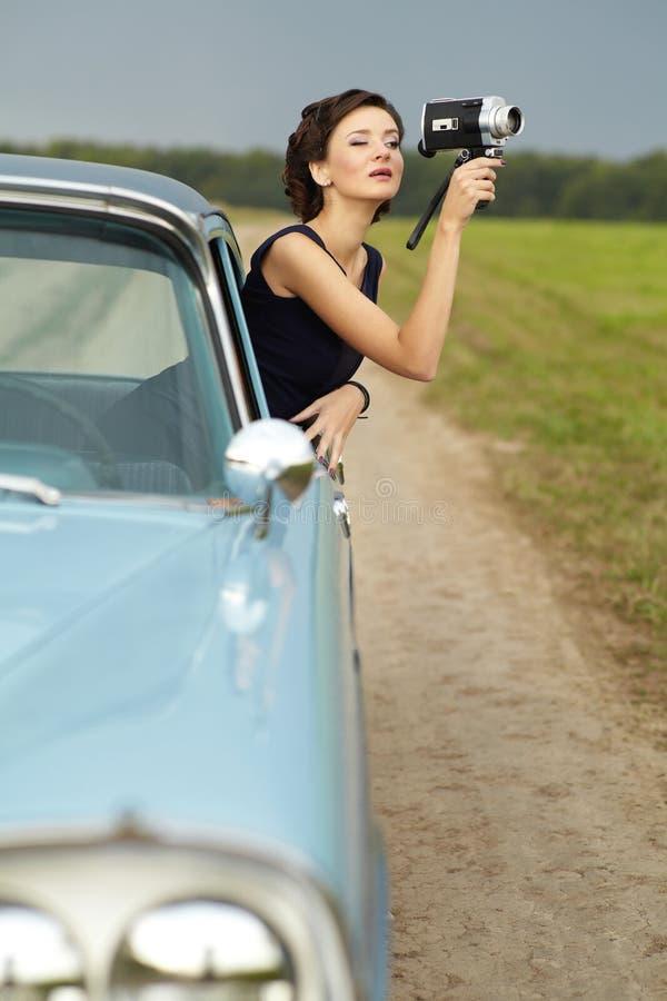 Όμορφη κυρία με μια αναδρομική φωτογραφική μηχανή κινηματογράφων στοκ εικόνες