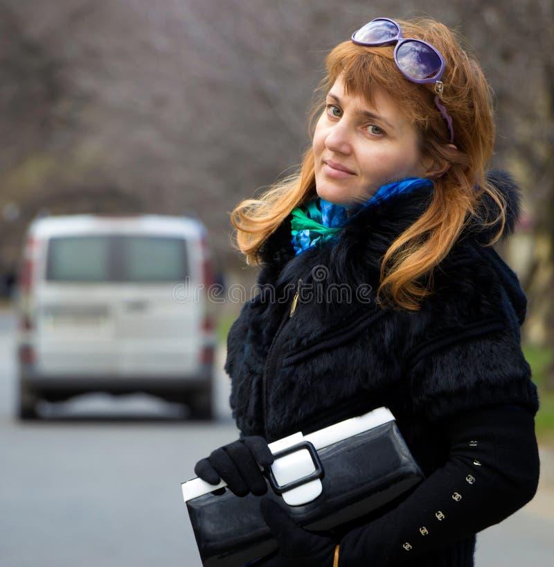 Όμορφη κυρία με το πορτοφόλι και θολωμένο αυτοκίνητο πίσω από την στοκ φωτογραφία