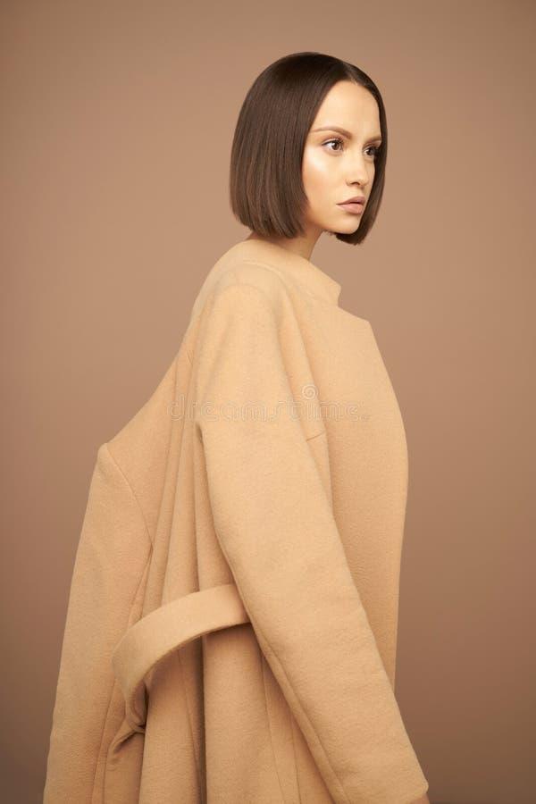 Όμορφη κυρία μόδας στο μπεζ παλτό στοκ φωτογραφίες