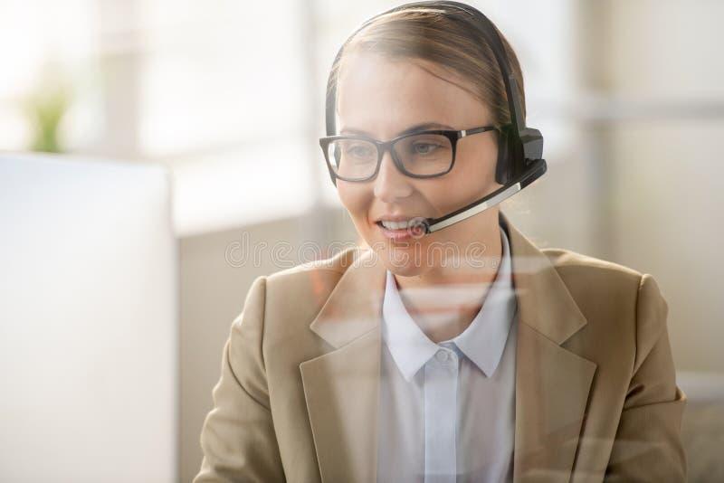 Όμορφη κυρία που εργάζεται στο τηλεφωνικό κέντρο της προγραμματίζοντ στοκ φωτογραφία