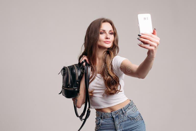 Όμορφη κυρία στην άσπρη μπλούζα και τζιν που εξετάζουν την στοκ φωτογραφία