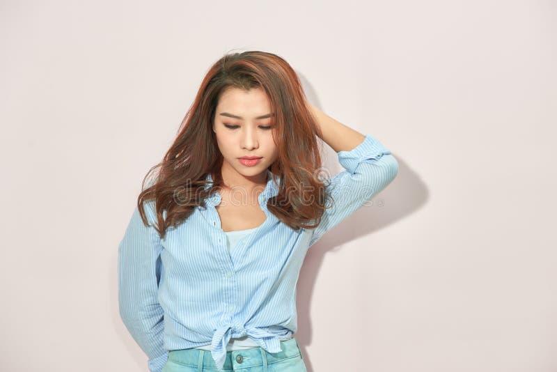 Όμορφη κυρία στην καθιερώνουσα τη μόδα μπλε μπλούζα που εξετάζει τη κάμερα με τη βέβαια έκφραση προσώπου στεμένος στο ανοικτό ροζ στοκ εικόνα