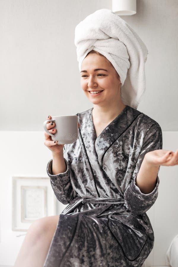 Όμορφη κυρία στη συνεδρίαση τηβέννων βελούδου με την πετσέτα στο κεφάλι και το φλυτζάνι υπό εξέταση στο σπίτι στοκ εικόνες με δικαίωμα ελεύθερης χρήσης