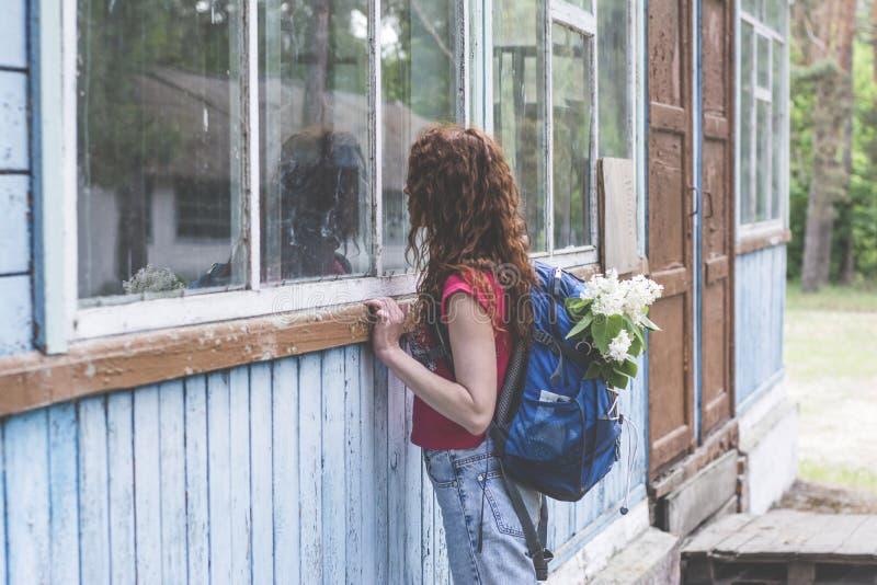 Όμορφη κόκκινη γυναίκα τρίχας με το σακίδιο πλάτης που κοιτάζει στο παράθυρο του τρομακτικού παλαιού σπιτιού στοκ φωτογραφία
