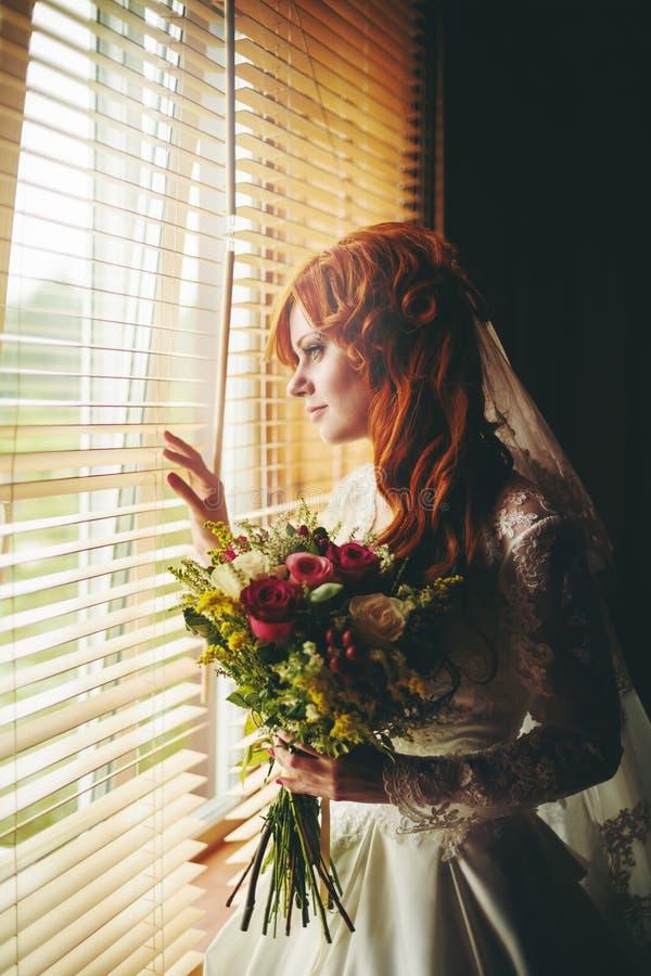 Όμορφη κόκκινη νύφη τρίχας κοντά στο παράθυρο στοκ εικόνες με δικαίωμα ελεύθερης χρήσης