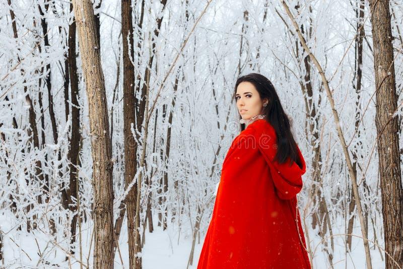 Όμορφη κόκκινη οδηγώντας πριγκήπισσα κουκουλών στο μαγικό χειμερινό δάσος στοκ φωτογραφίες με δικαίωμα ελεύθερης χρήσης