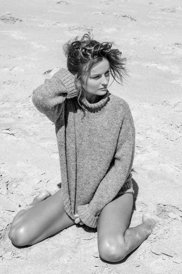 Όμορφη λεπτή συνεδρίαση γυναικών στην άμμο στην παραλία στοκ φωτογραφία με δικαίωμα ελεύθερης χρήσης
