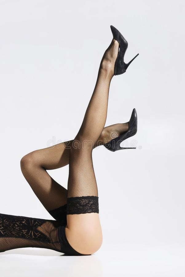 Όμορφη, λεπτή τοποθέτηση γυναικών στο δελεαστικό εσώρουχο και γυναικείες κάλτσες στοκ φωτογραφία