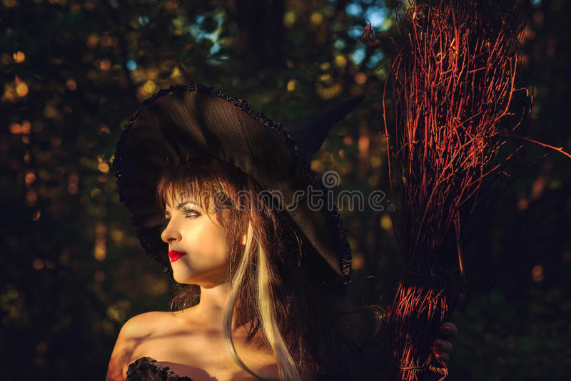Όμορφη μάγισσα γυναικών με το καπέλο και τη σκούπα στοκ εικόνες