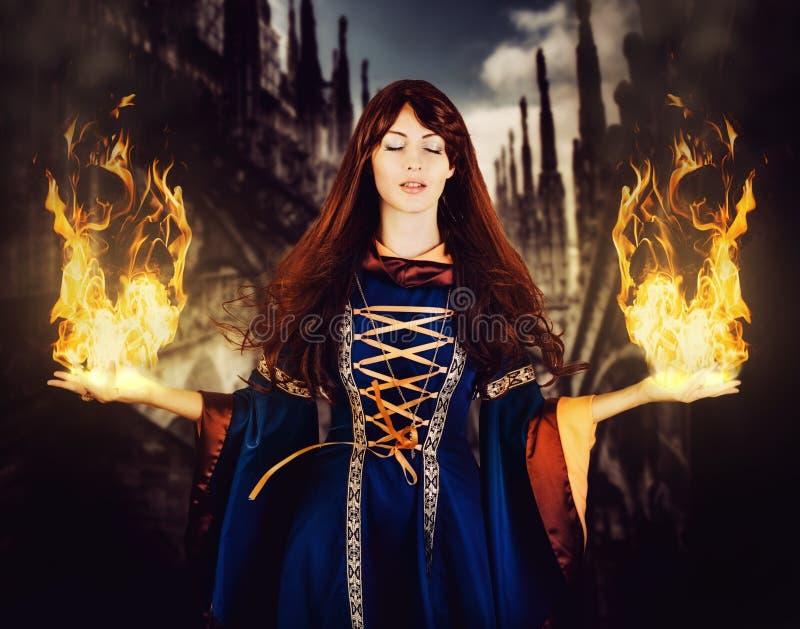 Όμορφη μάγισσα γυναικών στο μεσαιωνικό φόρεμα φαντασίας Πυρκαγιά μαγική στοκ εικόνες