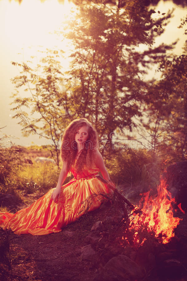 Όμορφη μάγισσα στα ξύλα κοντά στην πυρκαγιά Μαγική γυναίκα celebrat στοκ εικόνες
