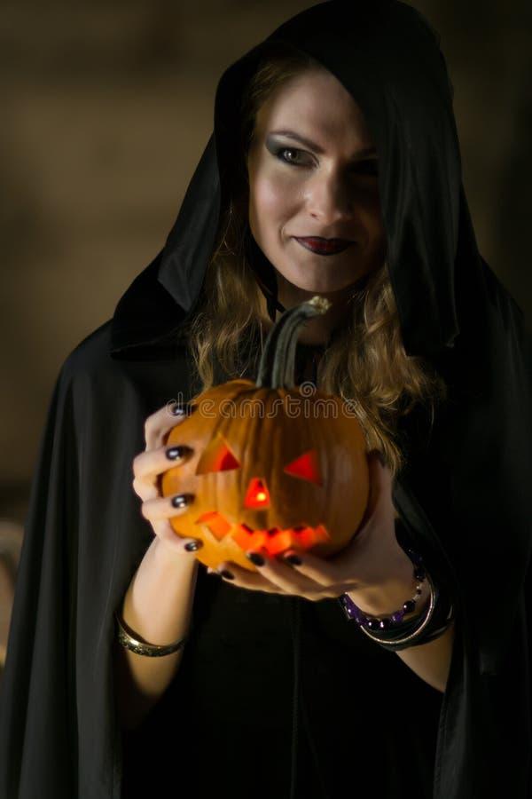 Όμορφη μάγισσα στο μαύρο μανδύα με ένα πρόσωπο κολοκύθας σε αποκριές στοκ φωτογραφία